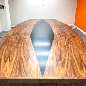 large finished medium and dark stained wood conference table in place in conference room