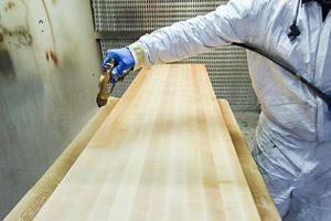 man spraying finish onto butcher board