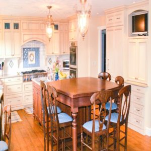 off white painted cabinets in classic look kitchen offset by medium brown stained island with seating for six
