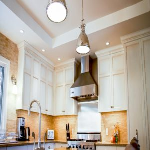 white pigmented cabinets surround rich brown tiles and stainless steel appliances