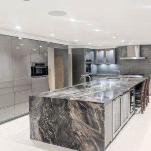 marbled special effect finish on large island in kitchen with grey pigmented cabinets