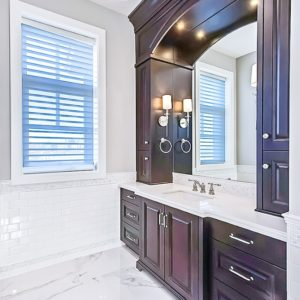 dark stained bathroom cabinets with white granite countertops and marble floors