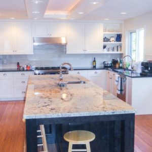 white kitchen cabinets and large dark stained island in modern kitchen with black and white granite countertops