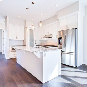 white painted kitchen cabinets with oversized stainless steel fridge and large island