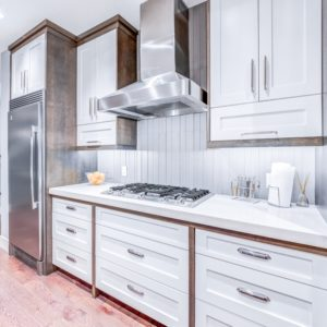 white pigmented cabinets surrounded by medium brown stained wood trim in modern kitchen