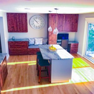 bright sunny kitchen with dark red stained cabinets and pigmented island cabinets