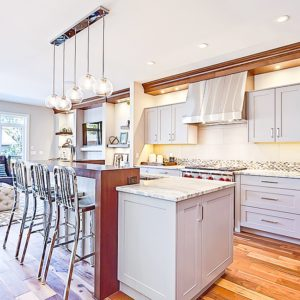 pigmented white cabinets in ultra-modern kitchen with gas stove and quartz countertops