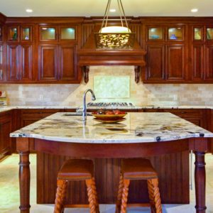 dramatic view of large unique island in kitchen with deep, rich brown stained wooden cabinets